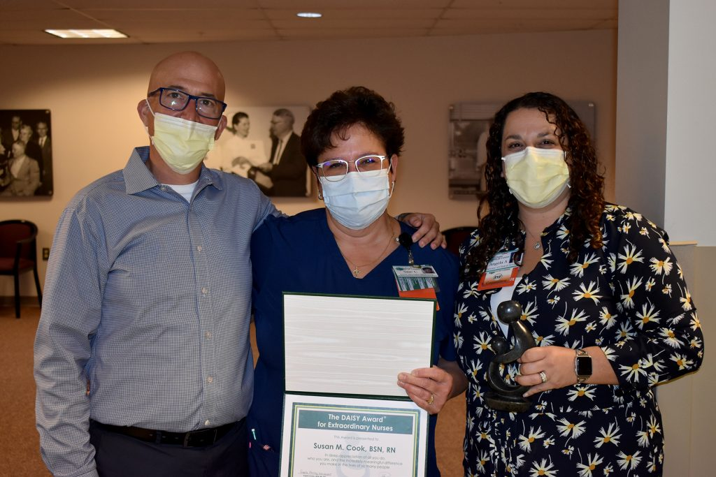 ERMC president and chief executive officer Tim Johnson (left) and director of clinical services Angela Ackley, MSN, RN (right) presenting the award to Susan Cook, BSN, RN (center).
